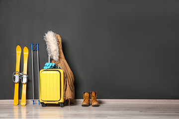 Garden Poster Winter sports Suitcase, jacket and skis on floor against black wall, space for text. Winter vacation