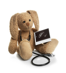 Ultrasound photo of baby and toy rabbit on white background. Concept of pregnancy