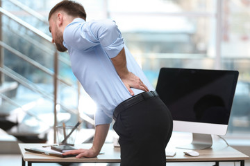 Businessman suffering from back pain at workplace