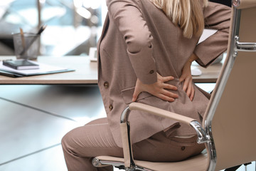 Young woman suffering from back pain in office, closeup