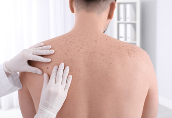 Doctor examining patient in clinic. Visiting dermatologist