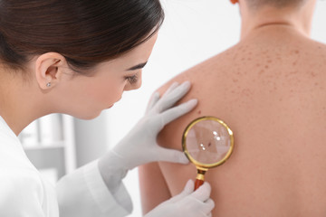Dermatologist examining patient with magnifying glass in clinic, closeup view
