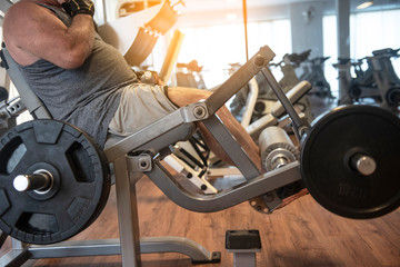 A senior man doing strength workout exercise with weight machine in gym. Copy space. - Image