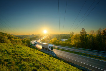 Three white trucks driving on the asphalt highway in autumn landscape in the rays of the sunset