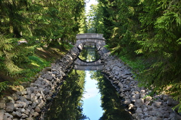 Old round stone bridge in the coniferous forest over a long narrow ditch with blue water between the stone walls in a beautiful city garden. Horizontal frame