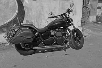 black and white motorcycle with leather seat and leather luggage bag, parked against the wall