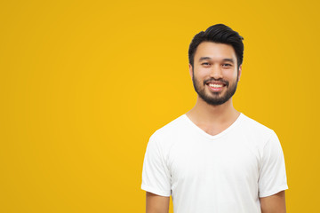 Asian handsome man with a mustache, smiling and laughing isolated on yellow background Wall mural