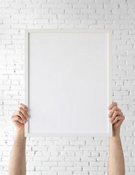 Holding frame mockup. Photo Mockup. Man hands hold frame. For frames and posters design. Frame size 16x20 (40x50cm).