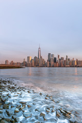 View on Financial  district from Hudson river beach at sunrise with long exposure