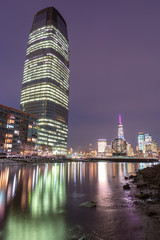 View on Jersey City and Financial District from Hudson river at night with long exposure