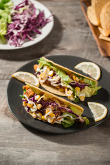Traditional mexican taco with chicken and vegetables on wooden table. Latin american food.