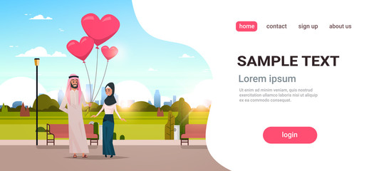 arab man giving woman pink heart shape air balloons happy valentines day concept arabic couple in love over city urban park cityscape background horizontal copy space