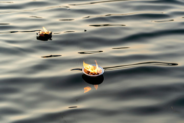 Hinduism religious ceremony puja flowers and candle on river Ganges water, India