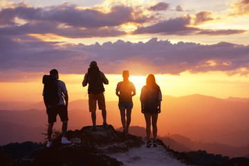 Group of four tourists or friends stands on mountain top and looks at sunset. Peoples travel concept