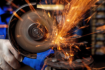 Close-up of a man sawing metal with a hand circular saw,  bright flashes flying in different directions, in the background tools for an auto repair shop. Work of auto mechanics.