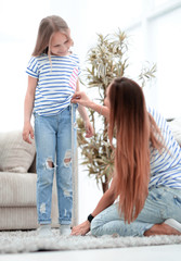 mom checks the length of her daughter's jeans