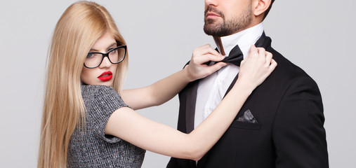 Sensual blonde woman adjusting tie bow for man, desire