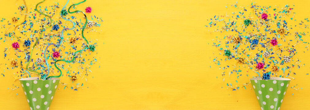 Party colorful confetti and clown hat over yellow wooden background . Top view, flat lay.