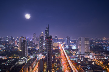 scenic of night cityscape with full moon on twilight skyline