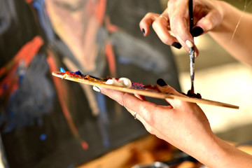 Close up of woman's hand mix paints with brush in pallete in art-class