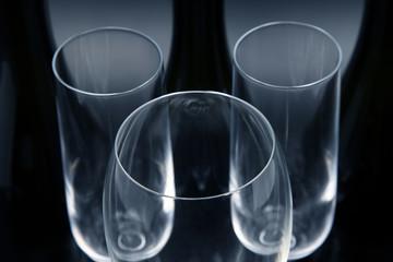 Three empty wine bottles and three empty wine glasses