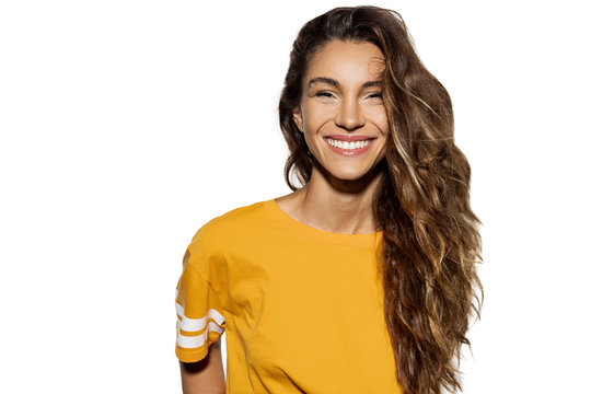 Portrait of long-haired brunette woman posing in studio on white background. Beautiful girl with healthy dark hairstyle in yellow shirt. Copy space in left side. Fun and modern concept