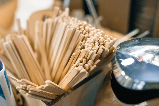 Many wooden drink coffee sticks stirrers, background cafe interior