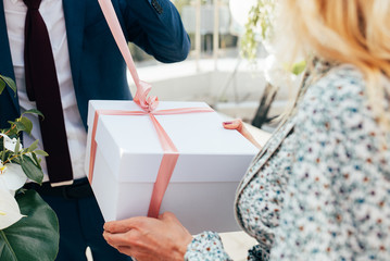 Female hands holding beautiful big gift wrapped with satin ribbon