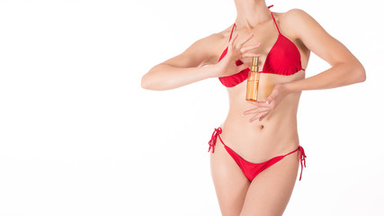 Sexy fit woman in red classic bikini with oil spray bottle, isolated on white