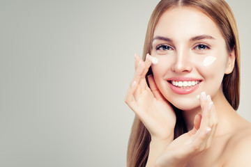 Exited beautiful woman with healthy clear skin applying moisturizing cream on her face, closeup portrait. Skin care, beauty and facial treatment concept
