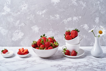Ripe organic strawberries in white ceramic bowls, cream and chamomile flowers in vase on gray concrete background, copy space. Healthy food concept, still life