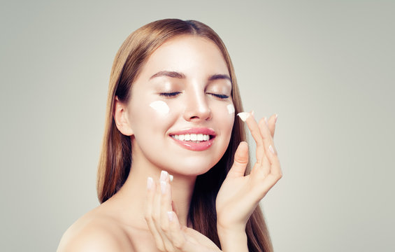 Young woman applying moisturizing cream on her healthy skin. Perfect face closeup. Skin care and facial treatment concept