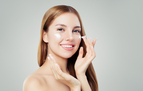 Happy young woman applying cream on her face. Skin care, beauty and facial treatment concept