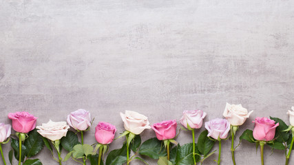 Flowers valentine day composition. Frame made of pink rose on gray background. Flat lay, top view, copy space.