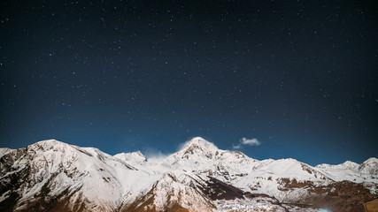 Georgia. Winter Night Starry Sky With Glowing Stars Over Peak Of Mount Kazbek Covered With Snow. Beautiful Night Georgian Winter Landscape
