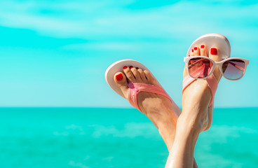Photo sur Plexiglas Pedicure Upside woman feet and red pedicure wearing pink sandals, sunglasses at seaside. Funny and happy fashion young woman relax on vacation. Chill out girl at beach. Creative for tour agent. Weekend travel.