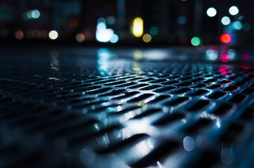 Shiny wet street sewer grate at night