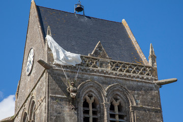 Historic church of Sainte mere l'eglise, with a paratrooper  hanging on the bell tower in Normady, France.