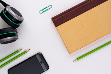 Top view of organized pencils, book, cellphone and headphones on a white desk background