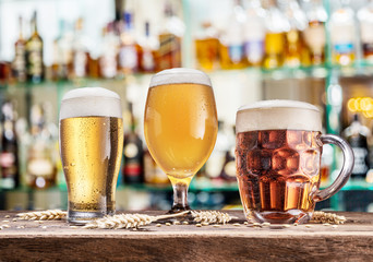 Wall Mural - Glasses of beer on the wooden table. Blurred pub interior at the background.