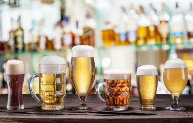 Wall Mural - Cold mugs and glasses of beer on the old wooden table. Pub interior and bar counter with beer taps at the background. Assortment of beer.