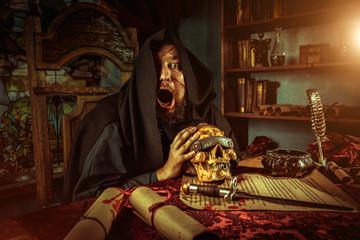 Necromancy sorcerer casting black magic spell using flaming skull