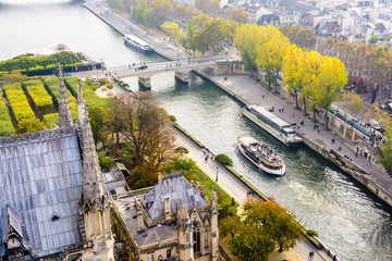 Aerial view from the tower of Notre-Dame de Paris cathedral over the river Seine with tour boats cruising and people strolling on the wharfs by a misty morning. Wall mural