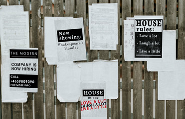 Sheets of paper ads on a wooden fence