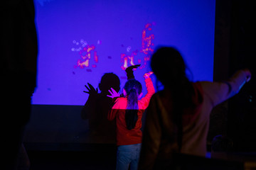 Abstract, blurry new technology background. Little girl is playing with interactive visual installation projected on wall