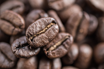 Three roasted coffee beans close up. Blurred coffee bean background. Top view.