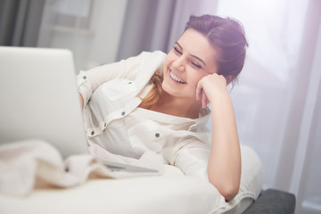 Young woman working with laptop lying on the bed in the bright and cozy bedroom at home