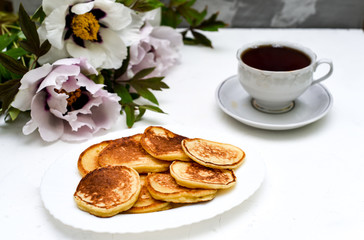tea and pancakes on the background of beautiful pions.