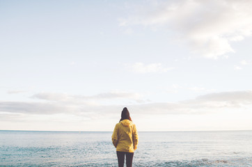 Portrait of a young woman on the beach wearing a yellow  raincoat and hat. Looking at the horizon.