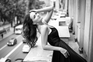 Black white portrait of young woman in elegant silk black dress lookingto a city from a balcony, fashion beauty photo
